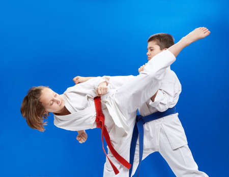 On a blue background boy and girl are hitting karate punches
