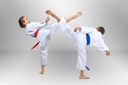Girl and boy are hitting a high kick leg