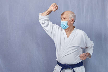 Old male athlete in a medical mask performs blocks with his hands Banque d'images