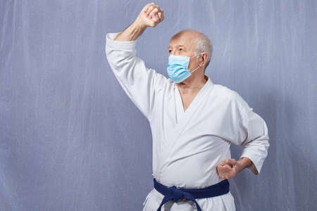 Old male athlete in a medical mask trains blocks with his hands