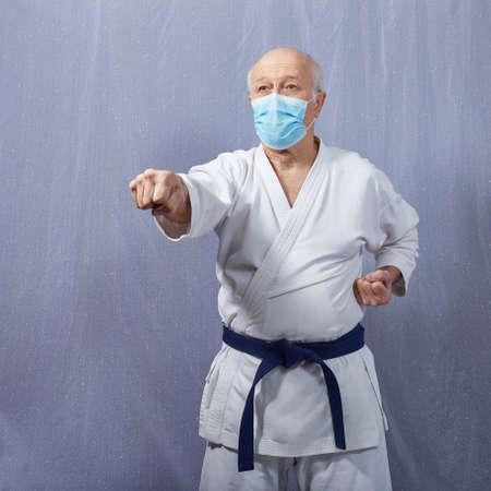 An old athlete with a blue belt and in a medical mask trains a punch arm