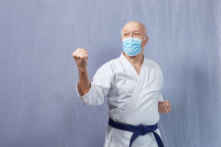 Blocks with hands performed by an old male athlete in a medical mask