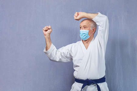 In a medical mask and karategi, an old man performs blocks with his hands