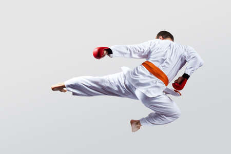 Man with red overlays on his hands trains a kick on a light background