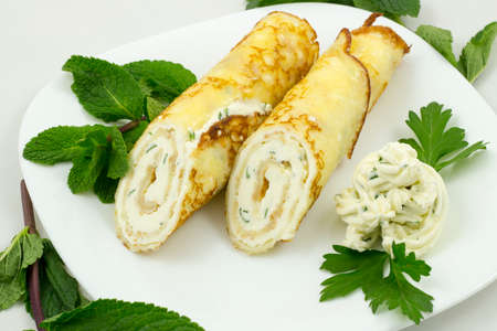 Crepes with cheese sauce on a white plate with mint leaves
