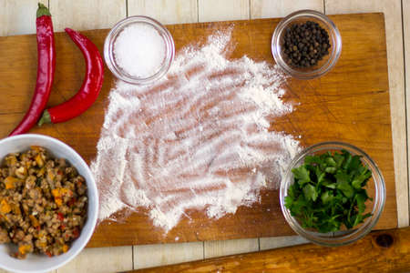 Empanadas cooking preparations: flour with spices, culinary herbs and minced pork on wood board Stock Photo - 72708990