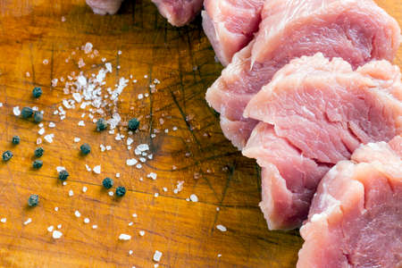 Cut raw pork on wood board with background of salt and black pepper Stock Photo - 72708891