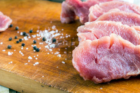 Cut raw pork on wood board with background of salt and black pepper Stock Photo - 72708987