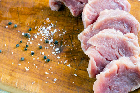 Cut raw pork on wood board with background of salt and black pepper Stock Photo