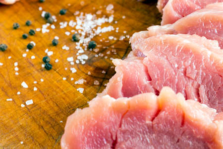 Cut raw pork on wood board with background of salt and black pepper Stock Photo - 72709161