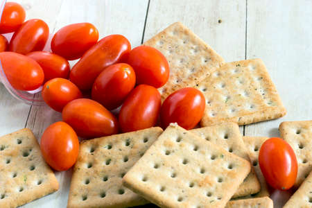 Cherry tomatoes with crackers on light wood background