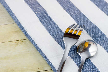 Fork and cloth napkin on light wood background Stock Photo