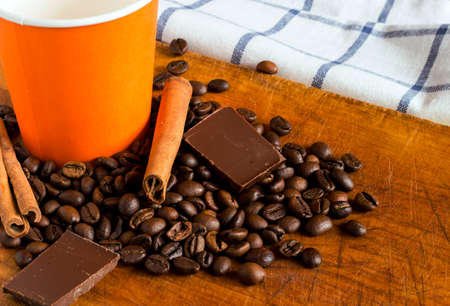 Coffee in orange paper glass with background of coffee beans, chocolate chunks and cinnamon sticks