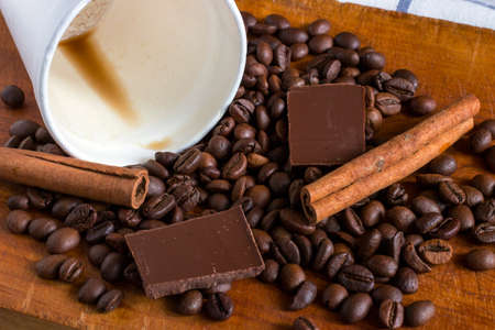 Coffee in white plastic glass with background of coffee beans, chocolate chunks and cinnamon sticks