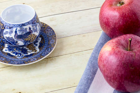Cup of tea with red apples on cloth napkin in light wood background