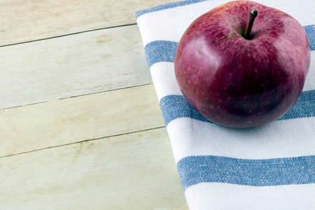 Red Apple and cloth napkin on light wood background Stock Photo