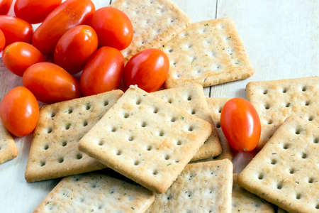 Cherry tomatoes with crackers on light wood background Stock Photo - 72552979