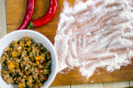 Empanadas cooking preparations: flour with spices, culinary herbs and minced pork on wood board Stock Photo