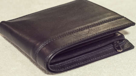 Leather black wallet on a light background close-up