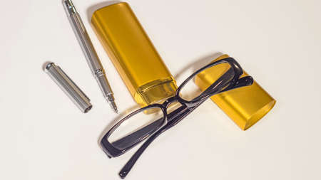 notelet: Black glasses, gold case and pen on the white background