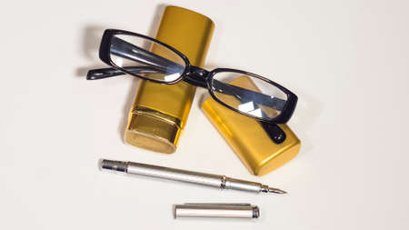 notelet: Glasses, gold case and a pen. Isolate white background.