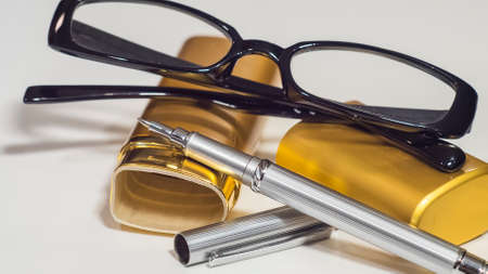 notelet: Glasses, gold case and a pen. White isolate background. Closeup. Stock Photo