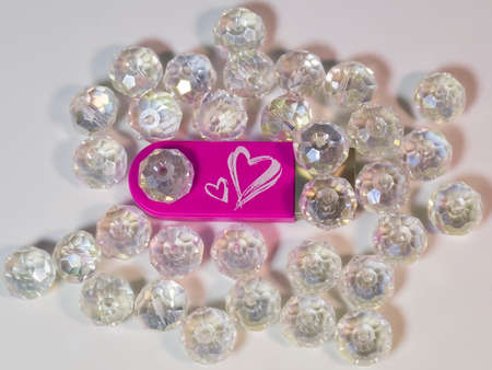 Pink USB flash drive with heart, gems on light background
