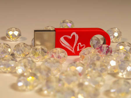 Red flash drive with heart and gems on light background Stock Photo