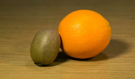 The fresh orange and kiwi on a wooden surface