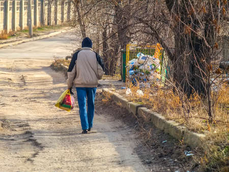 Man carries bag of trash to the dumpster