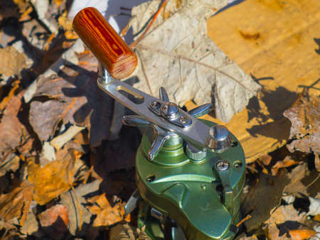 A reliable fishing reel on leaves closeup