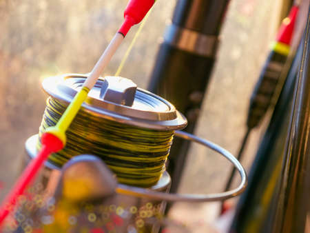 The bright red yellow float and fishing reel close-up