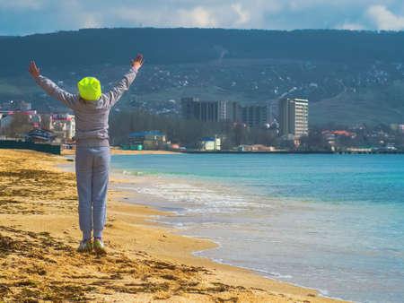 A girl near the sea joyfully raises her arms up Stock Photo