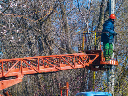 Worker in special clothes and helmet on the loong machine lift at an electric pole 免版税图像
