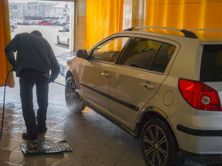 thoroughly: The worker thoroughly washes the silver car