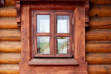 A window with a wooden profile in a house made of beams. Imagens