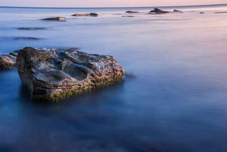 Seascape at sunset. Sea on a long shutter with stones and rocks.