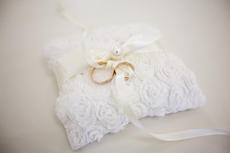 A pair of wedding rings on a white pillow. The top of the pillow is made of lace fabric in the form of roses. Rings intertwined a white ribbon Фото со стока