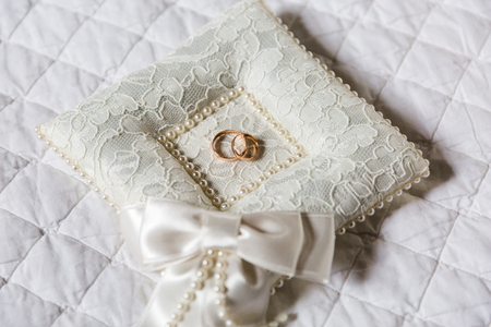 A pair of wedding rings on a white pillow. The pillow has a lace texture, in the center of the pillow is a recess in which the rings are. 스톡 콘텐츠