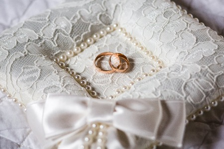 A pair of wedding rings on a white pillow. The pillow has a lace texture, in the center of the pillow is a recess in which the rings are. Close up photo