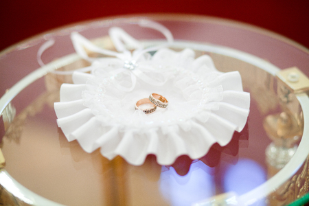 A pair of wedding rings on a white lace napkin. Napkin on the mirror surface