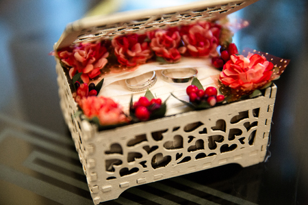 Wedding rings in a white wooden jewelry box with flowers