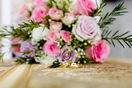 Close-up of a pair of wedding rings on the background of a wedding bouquet of flowers