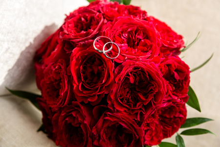 A pair of wedding rings on a bouquet of red flowers, close up shot