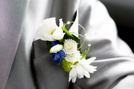 Wedding suit with boutonniere of white and blue flowers Фото со стока