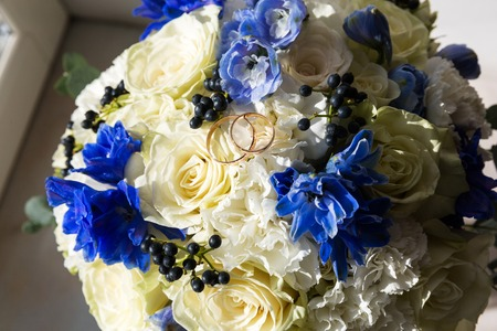 A pair of wedding gold rings on a bouquet of colorful flowers, close up shot