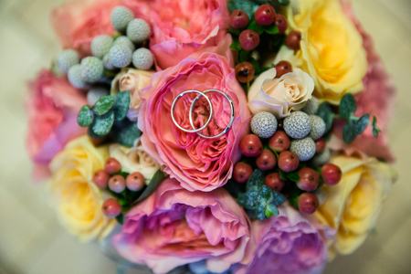 A pair of wedding rings on a bouquet of colorful flowers, close up shot