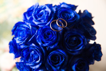 A pair of wedding rings on a bouquet of blue flowers, close up shot