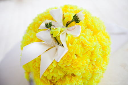 A pair of wedding rings on a bouquet of yellow flowers, close up shot