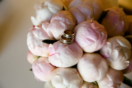 A pair of wedding gold rings on a bouquet of peonies, close up shot